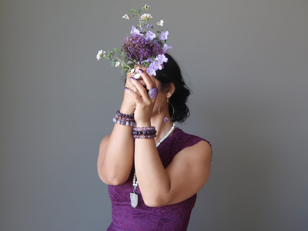 sheila of satin crystals dressed in purple holding purple and white flowers at her crown chakra