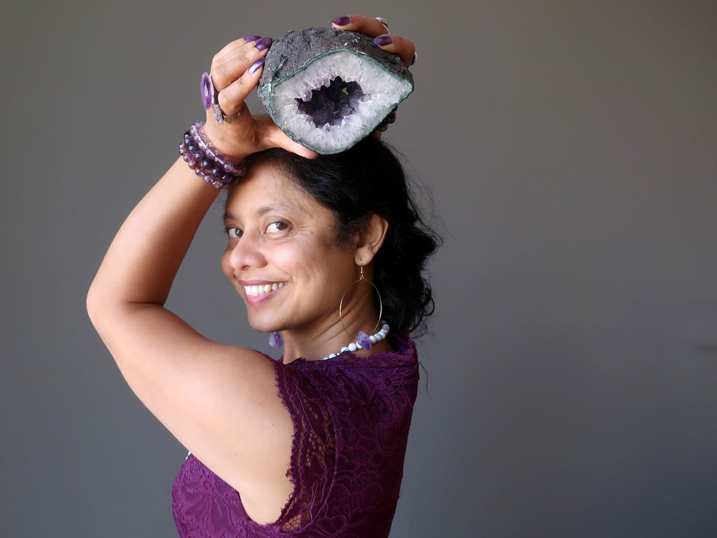 sheila of satin crystals holding an amethyst geode at her crown chakra