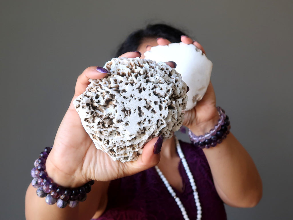 sheila of satin crystals holding up two white scolecite domes