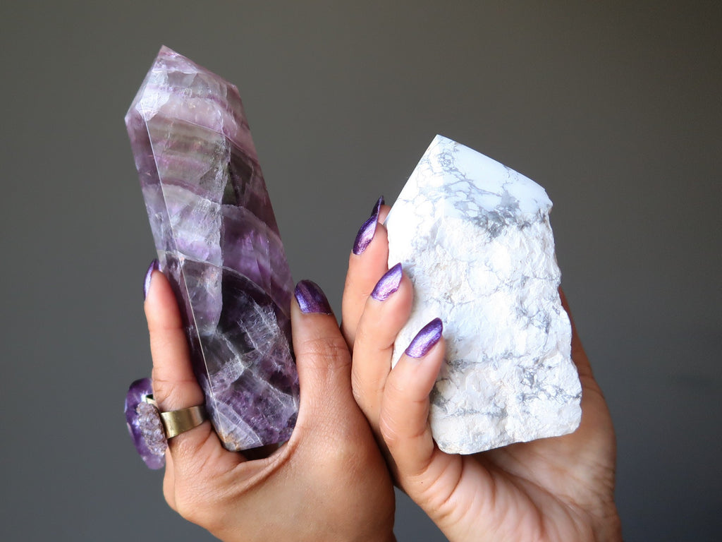 hands holding a fluorite tower and howlite tower