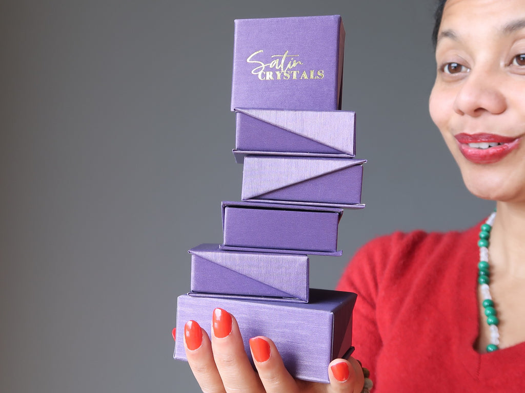 sheila of satin crystals holding a tall stack of purple gift boxes