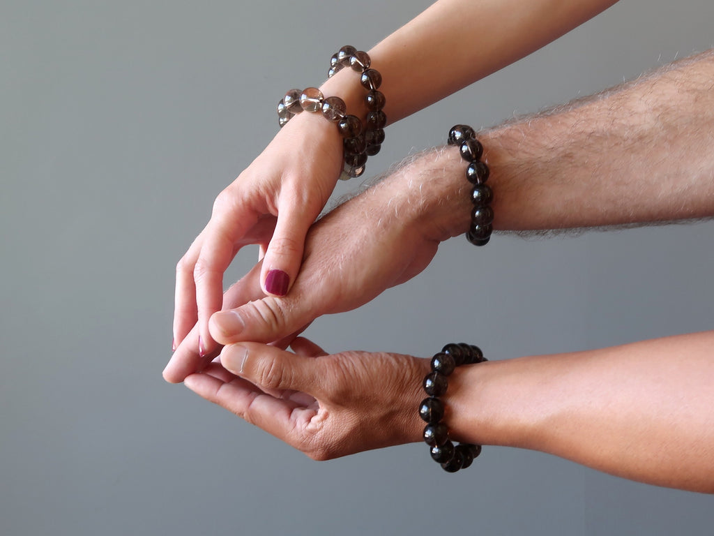 three hands wearing smoky quartz bracelets getting ready for group meditation