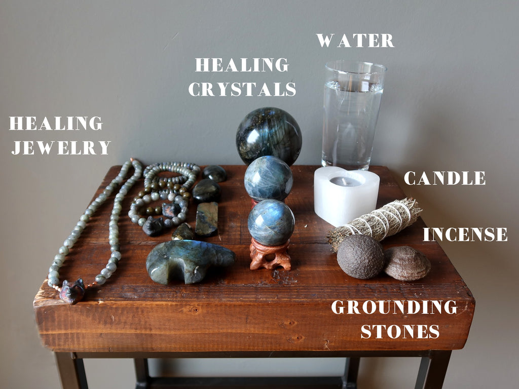 jewelry, crystals, water, candle, sage, grounding stones for meditation