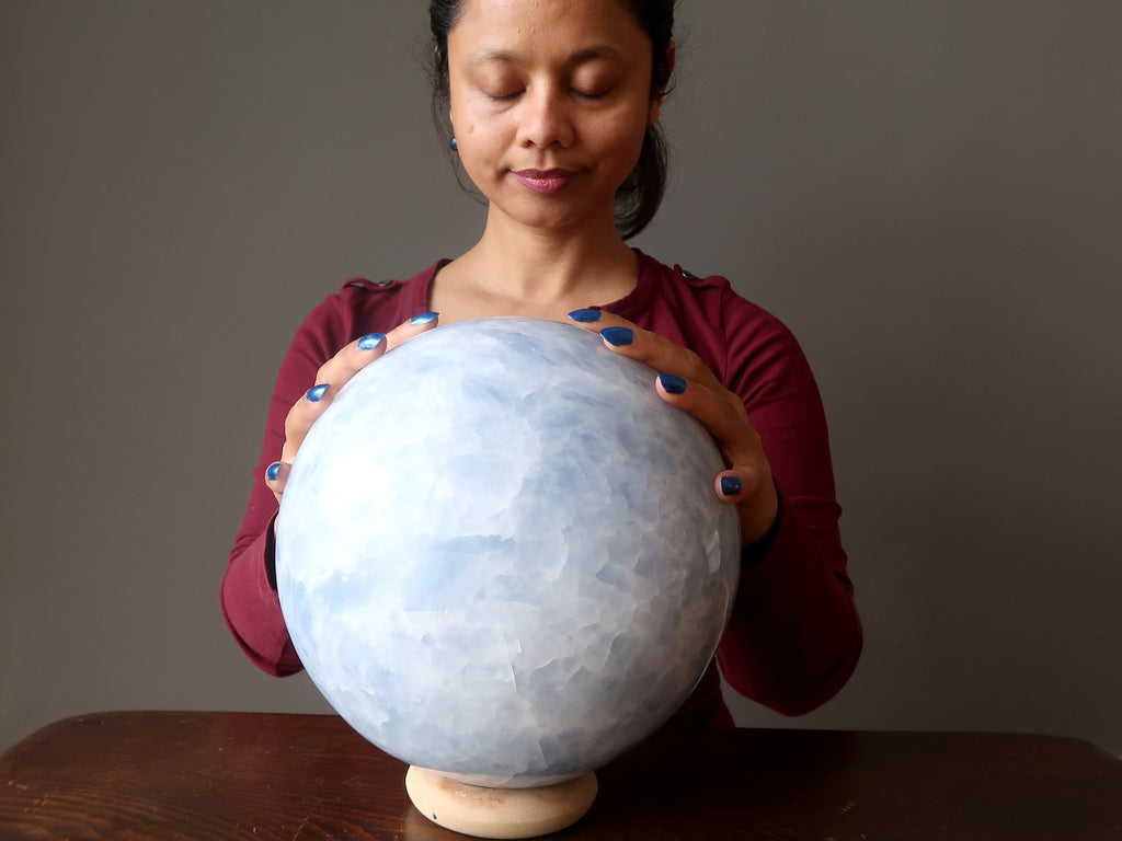 sheila of satin crystals with hands on a gigantic blue calcite sphere