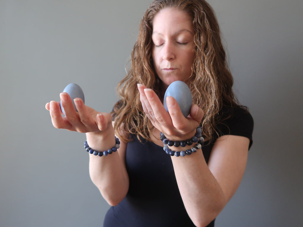 jamie of satin crystals holding two blue angelite stone eggs in her hands for meditation