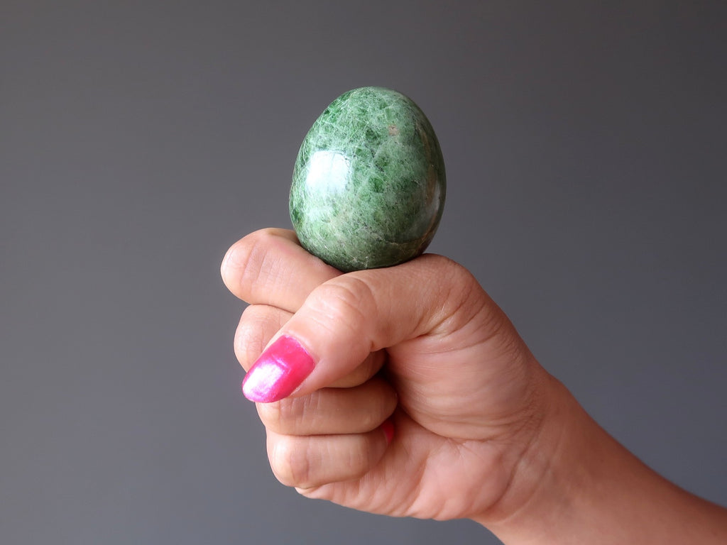 hand holding up a green diopside egg for crystal healing