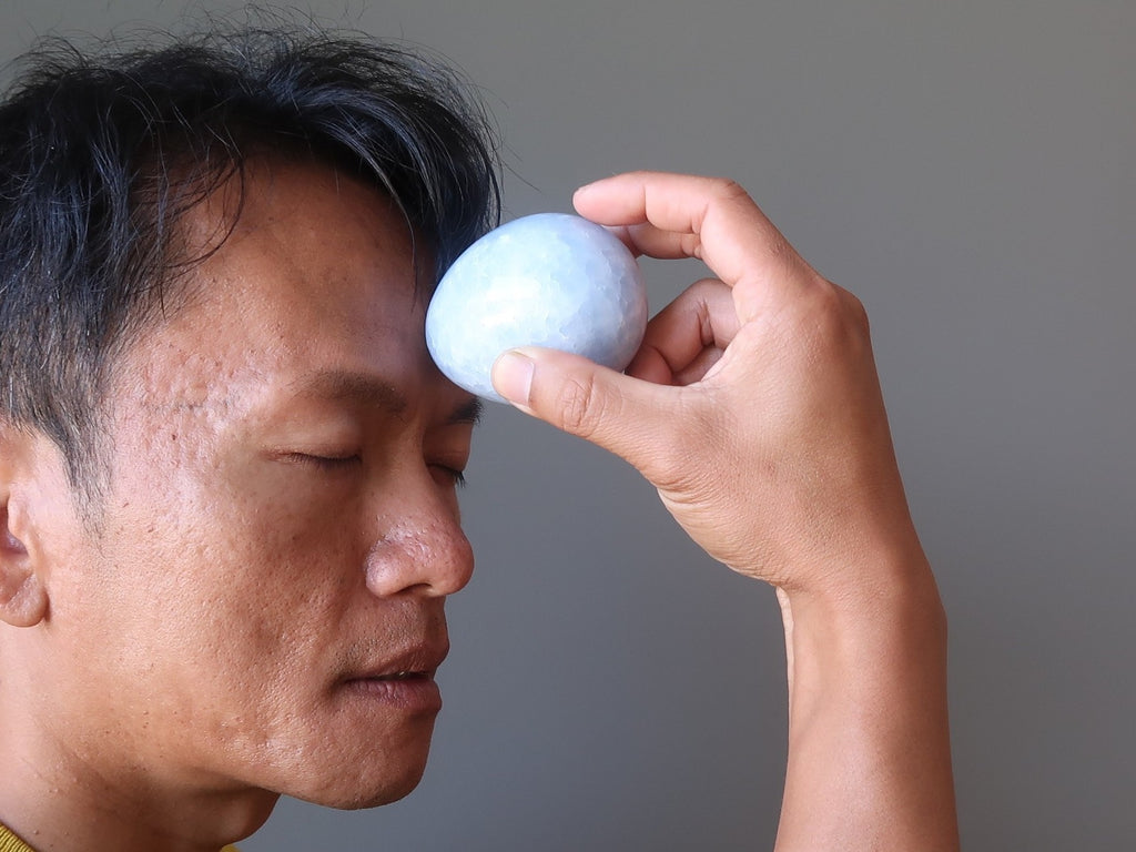 tim of satin crystals using a blue calcite stone egg for healing at the third eye chakra