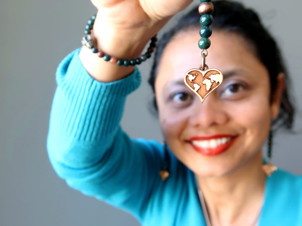 Brown wood heart shaped map charms dangling from bloodstone earrings in front of a female's third eye chakra with blue sweater, pyrite skull bracelet
