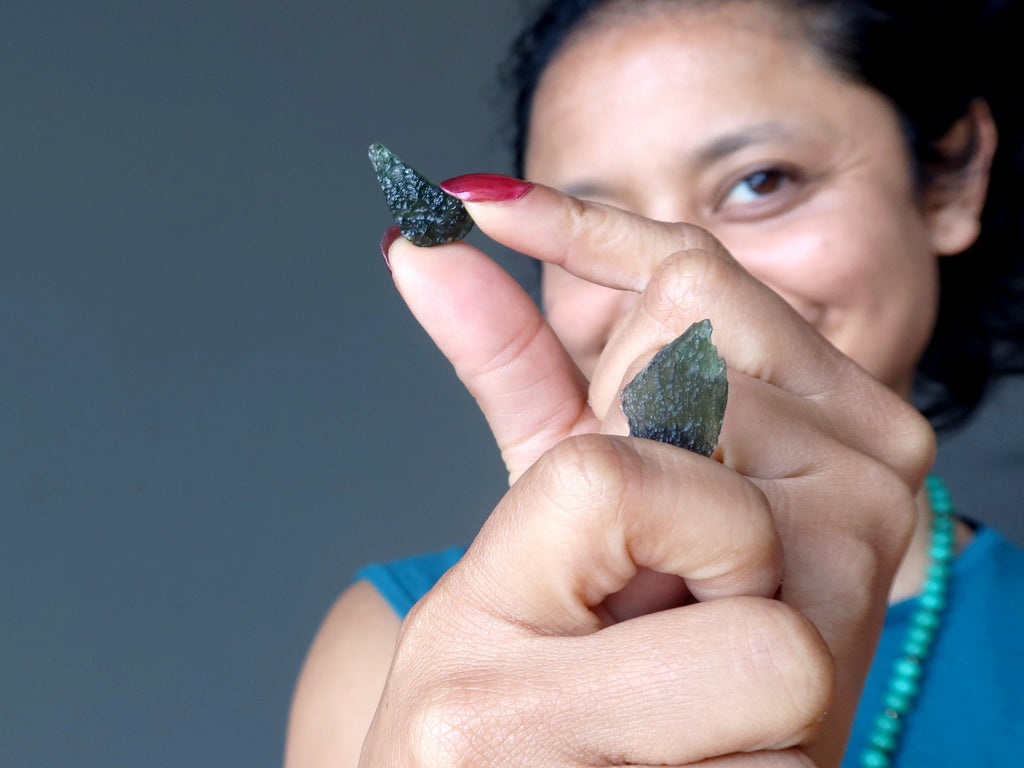 sheila of satin crystals holding two moldavite pieces