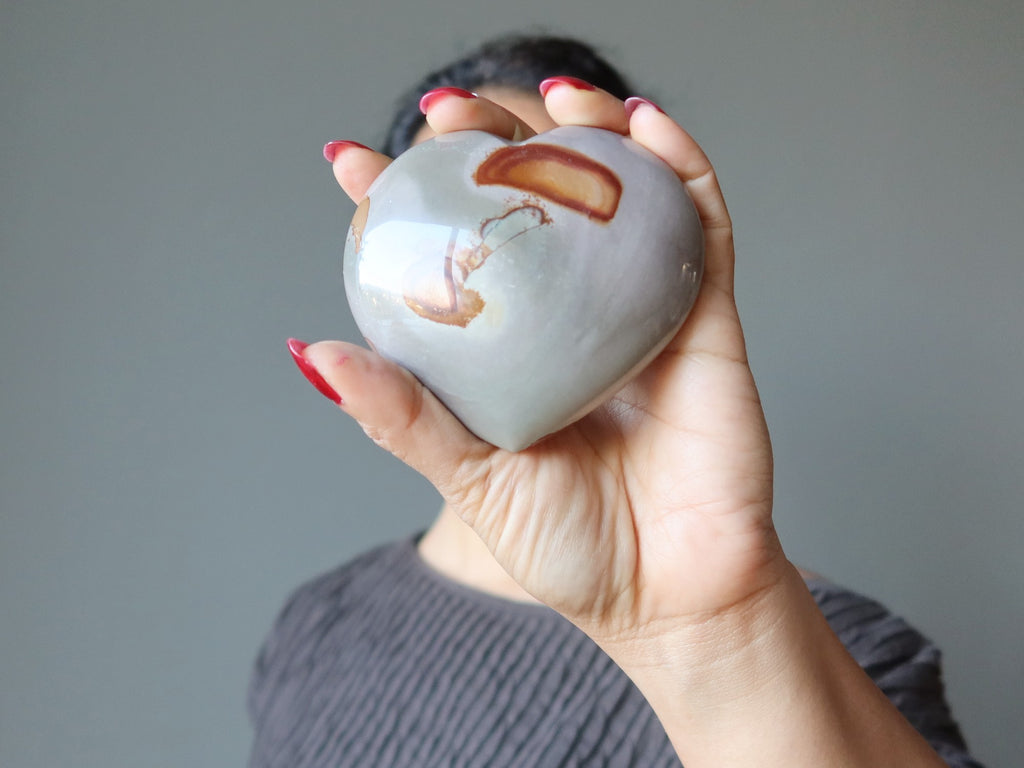 female holding a gray and orange polychrome jasper heart stone in front of her face