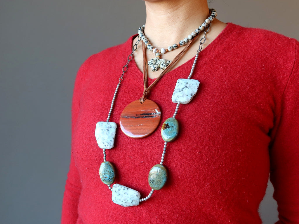 female torso in red sweater and jasper necklaces