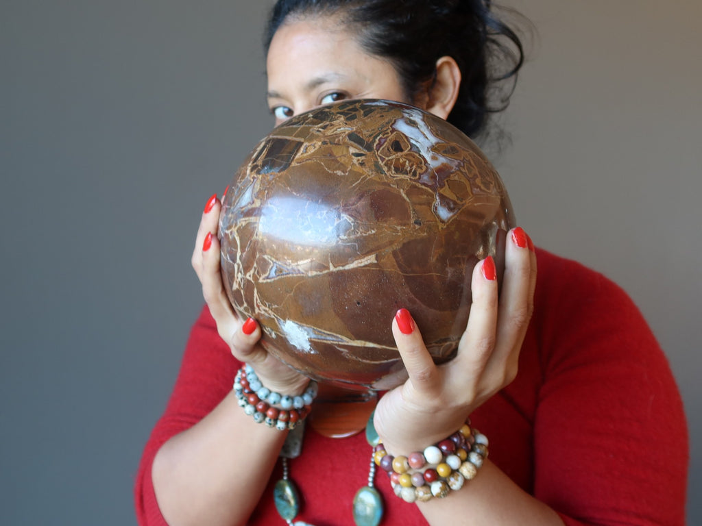 sheila of satin crystals holding a large brown jasper sphere