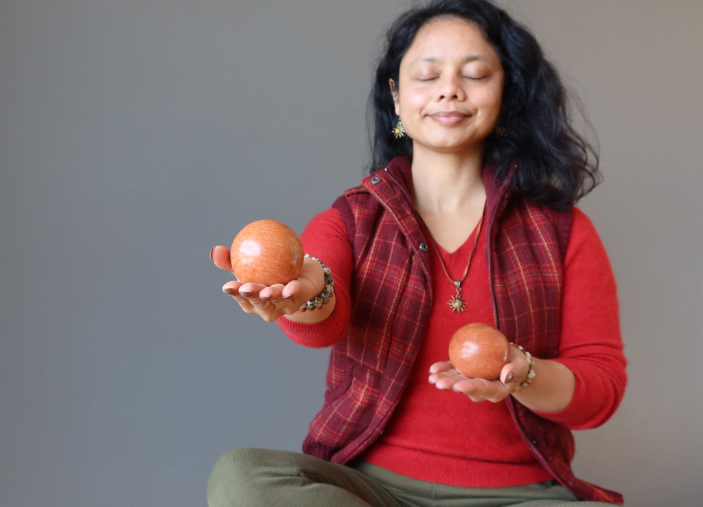 female meditating with two red jasper crystal balls