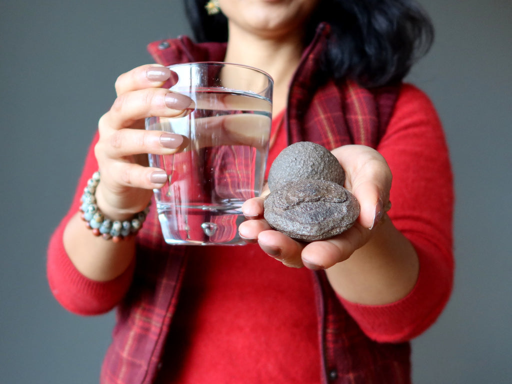 female holding moqui marbles and a glass of water