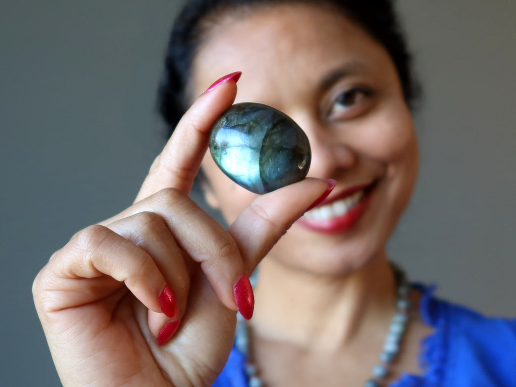 sheila of satin crystals holding a labradorite oval cabochon to her eye