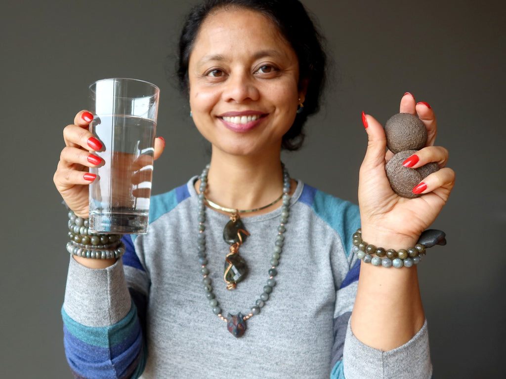 sheila of satin crystals holding a glass of water a pair of moqui marbles, wearing labradorite jewelry