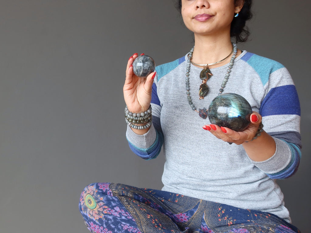 female sitting cross legged holding labradorite spheres