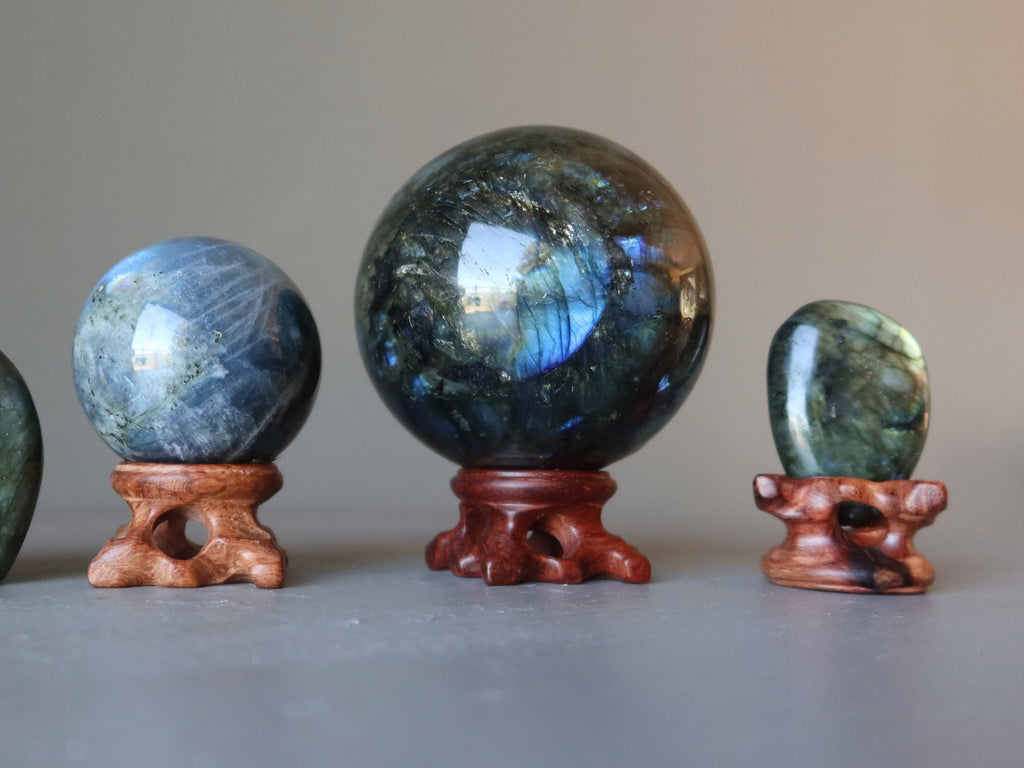 two labradorite spheres and a labradorite polished stone in wood display stands
