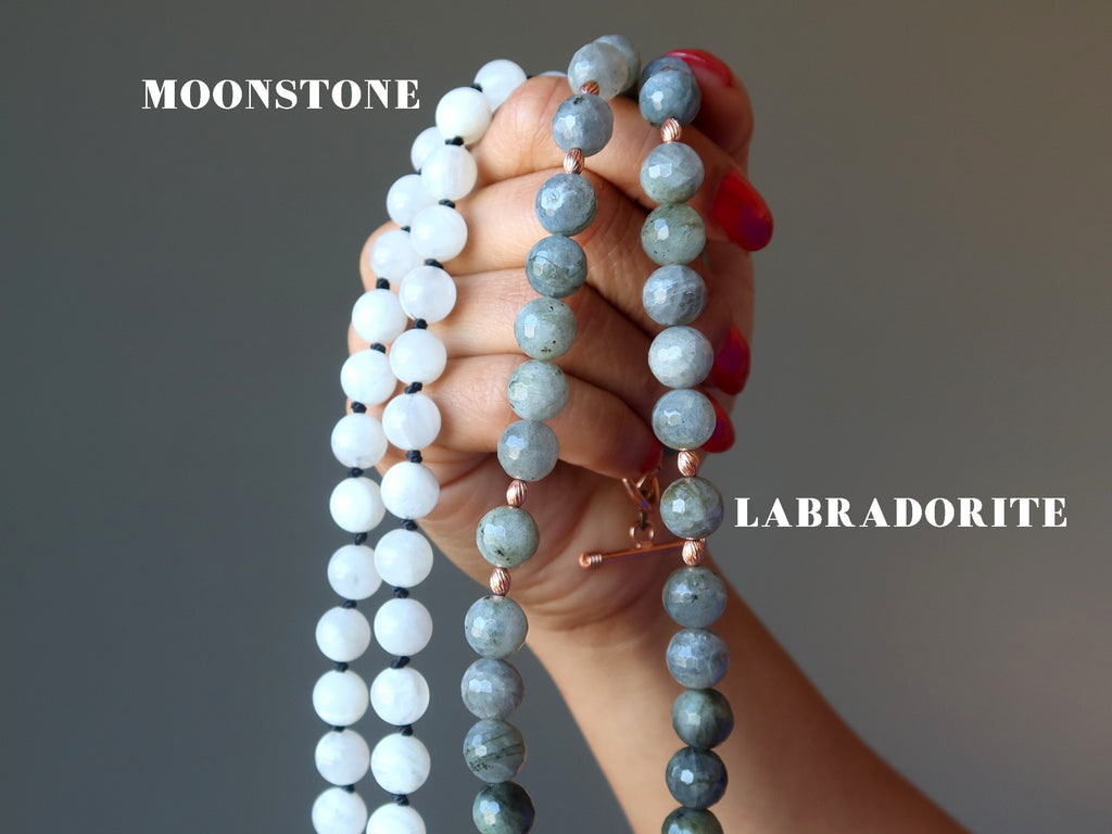 hand holding up white moonstone necklace and a faceted labradorite necklace