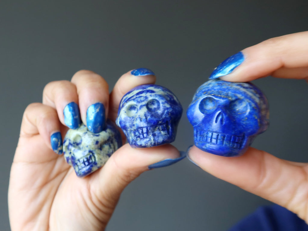 hands holding up three lapis lazuli skull figurines