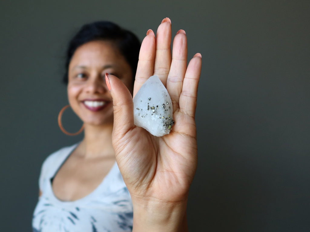 female model holding a quartz pyrite crystal in her palm
