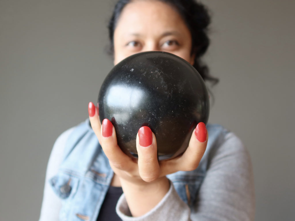 sheila of satin crystals holding a large black lava sphere