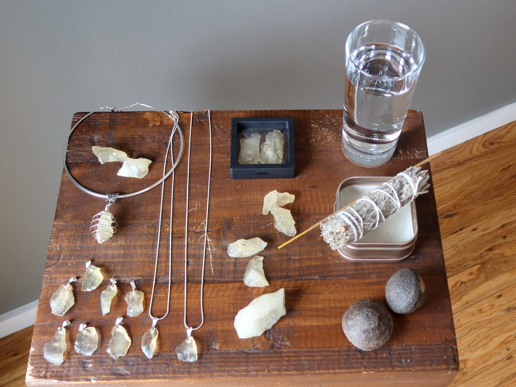 yellow libyan desert glass raw and jewelry, sage, candle, incense, moqui marbles, glass of water