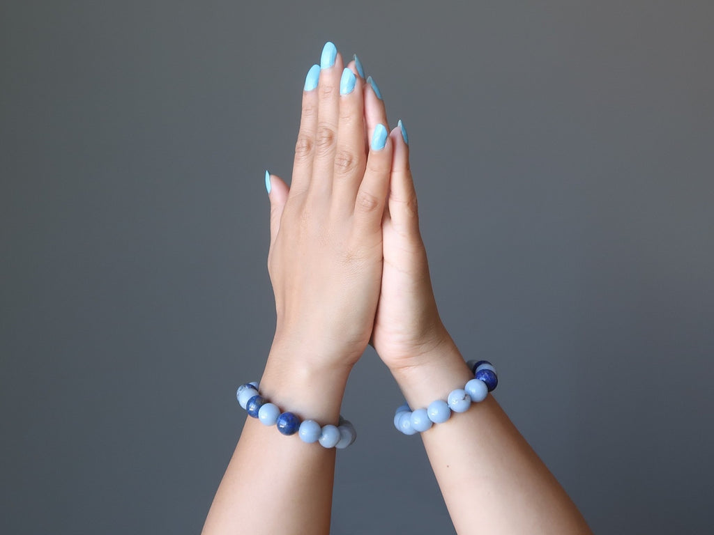 hands in meditation wearing lapis and angelite stretch bracelets