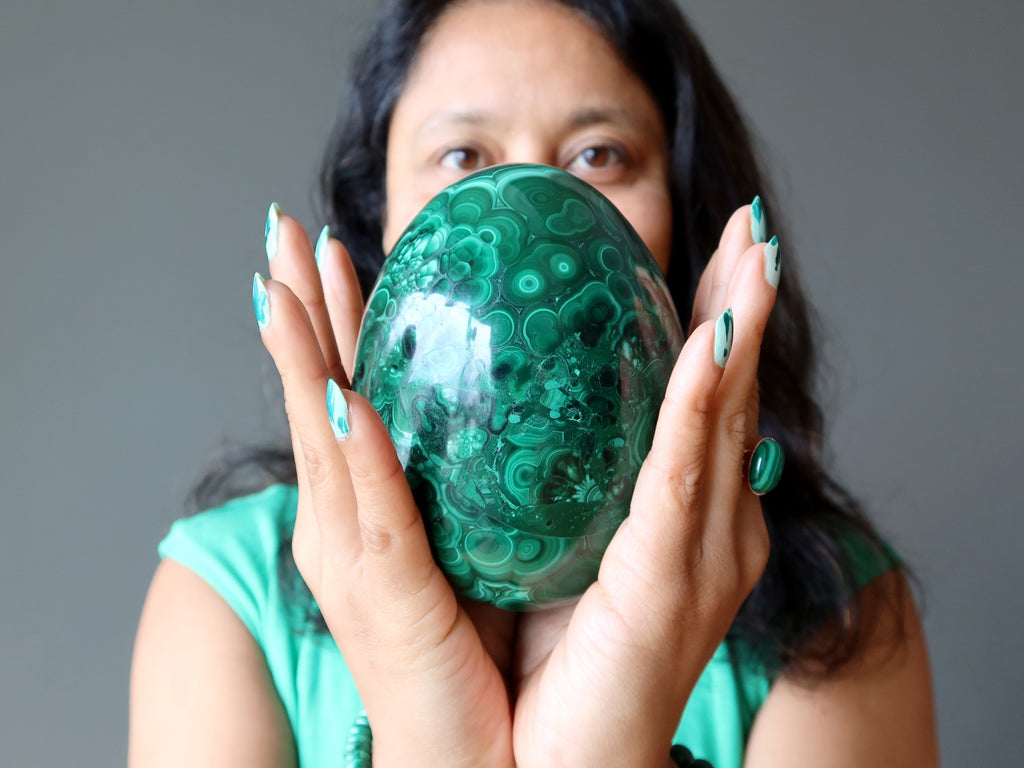 female holding large malachite egg in both hands