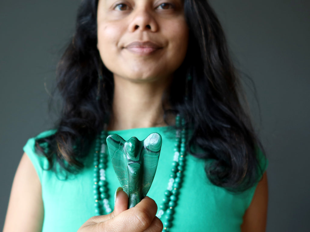 sheila from satin crystals holding up a malachite angel at her heart chakra