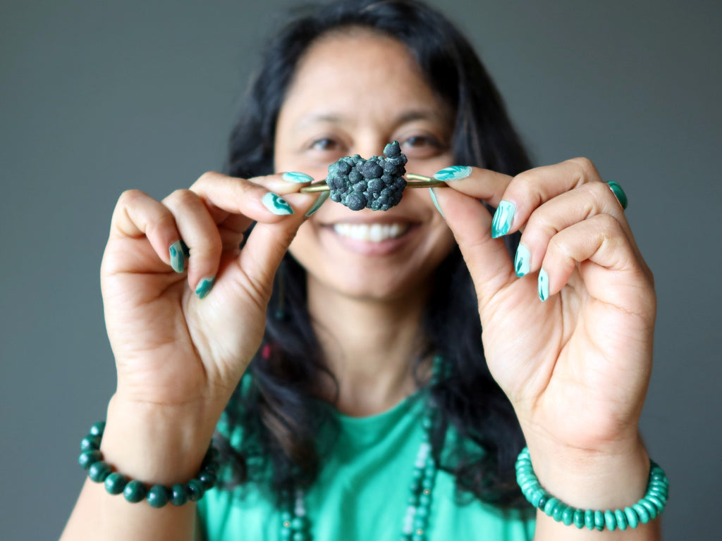 sheila of satin crystals holding up a raw malachite bracelet