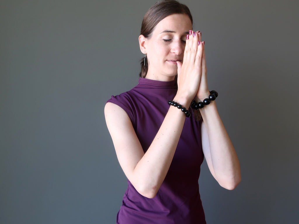 lucia of satin crystals wearing obsidian stretch bracelets in meditation pose