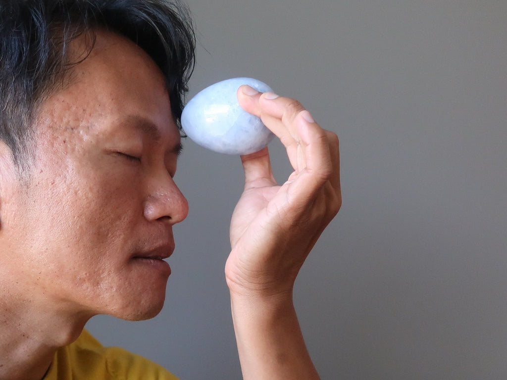 tim of satin crystals meditating with a blue calcite stone egg at his third eye chakra