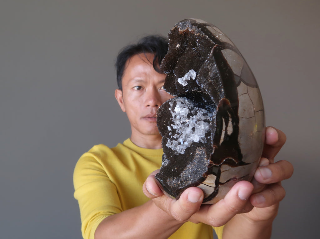 tim of satin crystals focusing on a giant septarian druzy quartz stone egg for meditation