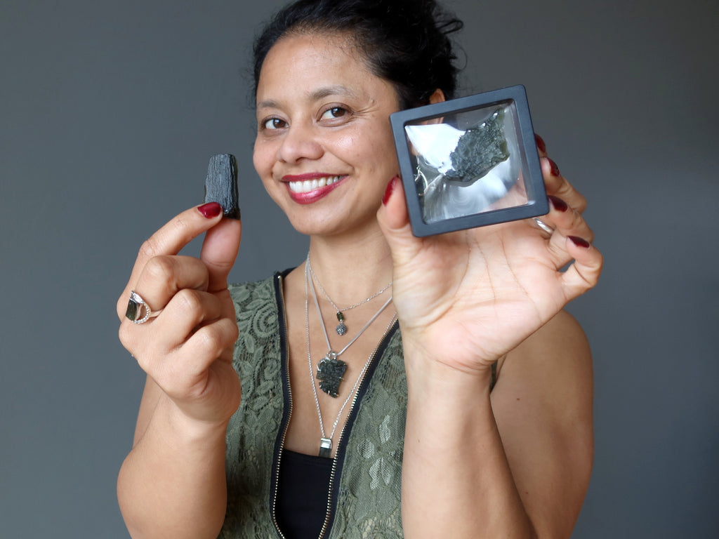 sheila of satin crystals holding and wearing moldavite