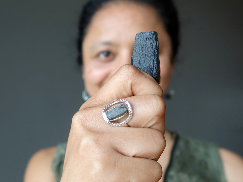 sheila of satin crystals holding a moldavite stone and wearing a moldavite ring