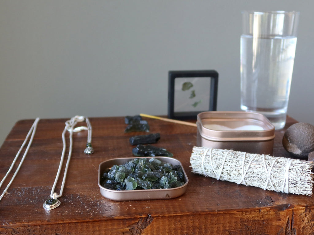 moldavite stones and jewelry with sage, incense, candle, moqui marbles and water