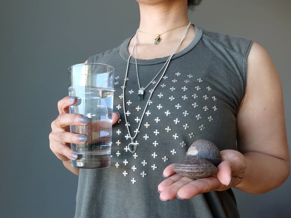 woman holding glass of water and pair of moqui marble stones