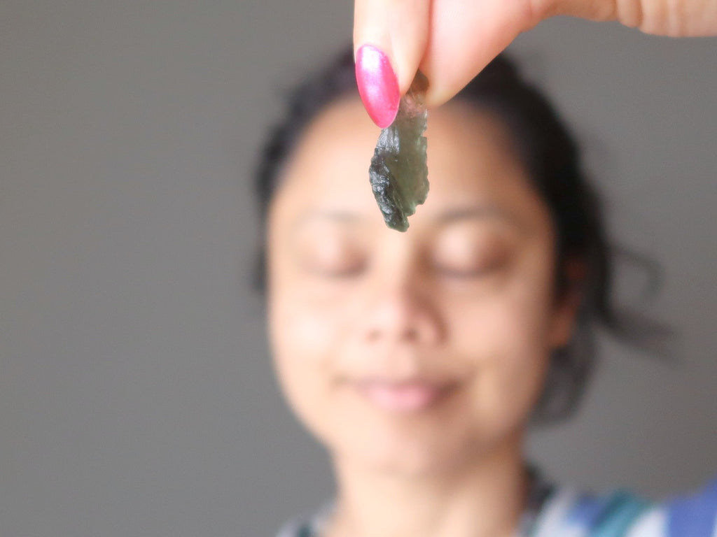 sheila of satin crystals holding up a gemmy green moldavite stone meteorite in front of her third eye chakra