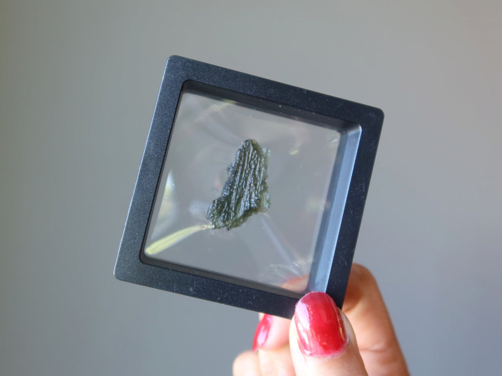 hand holding up a raw green moldavite in clear suspension display case