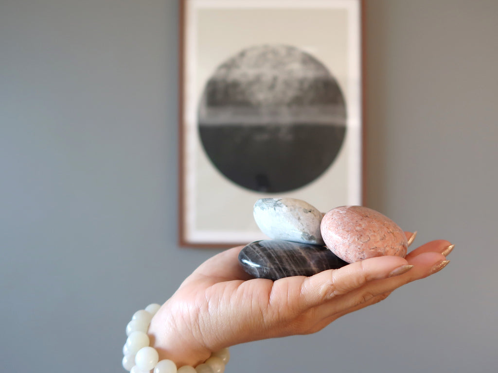 hand holding moonstone crystals in front of a full moon framed picture
