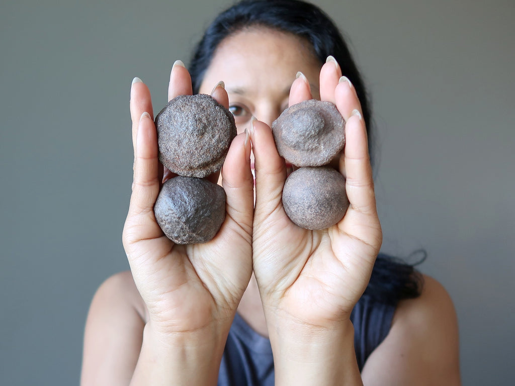 sheila of satin crystals holding 4 moqui marble stones in the palm of her hands