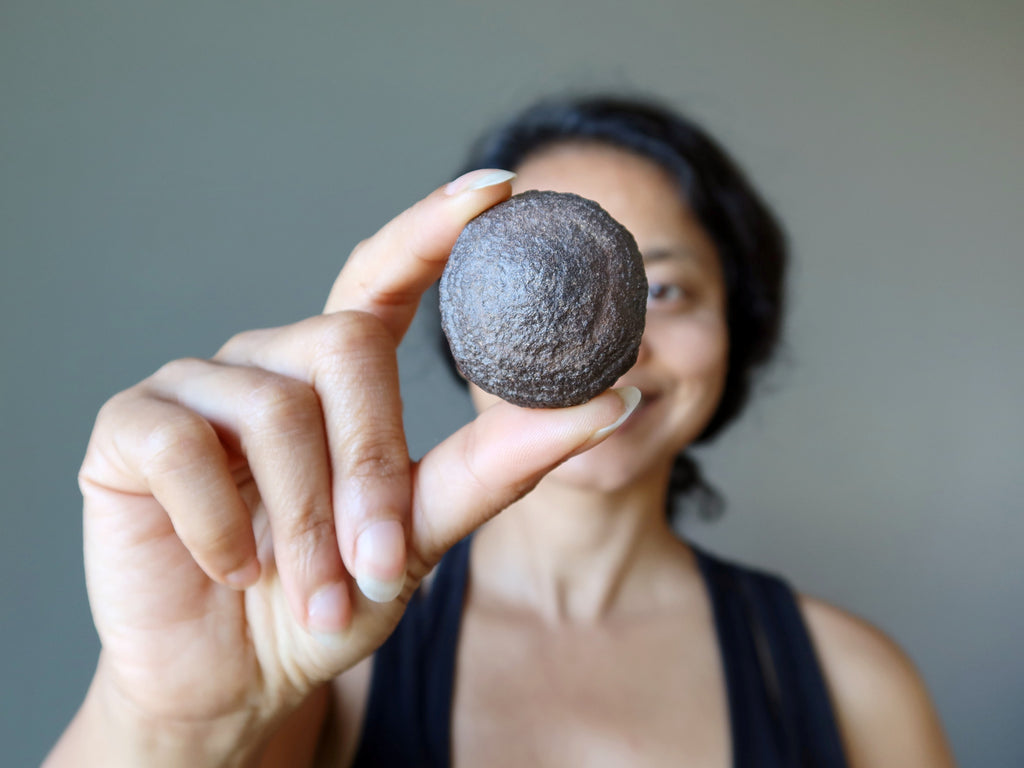 sheila of satin crystals holding a brown moqui stone ball