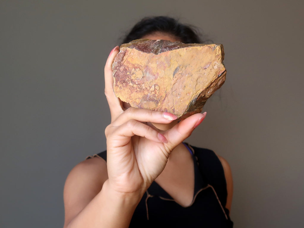 sheila of satin crystals holding up a raw slab of golden brown tigers eye stone for new beginnings