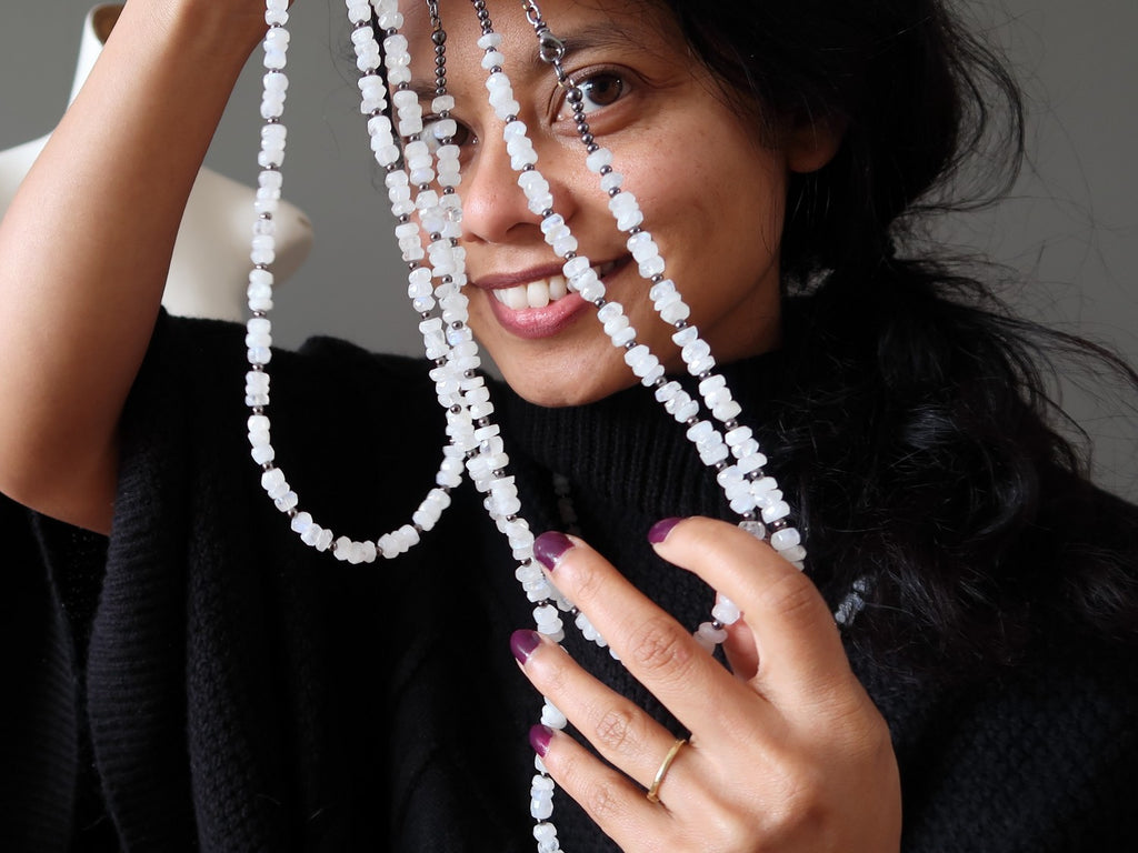 Satin Crystals jewelry designer with 3 strands of white Rainbow Moonstone necklaces in front of her face.