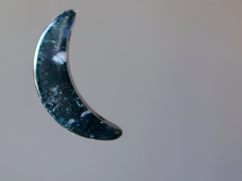 green and white moss agate crescent moon stone on gray background