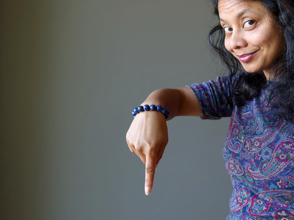 sheila of satin crystals wearing a lapis bracelet and pointing downwards