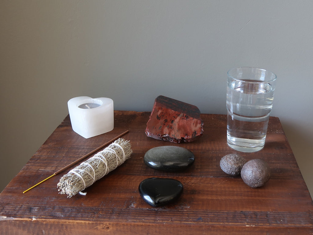 candle, incense, sage, obsidian stones, glass of water and moqui marbles on a table