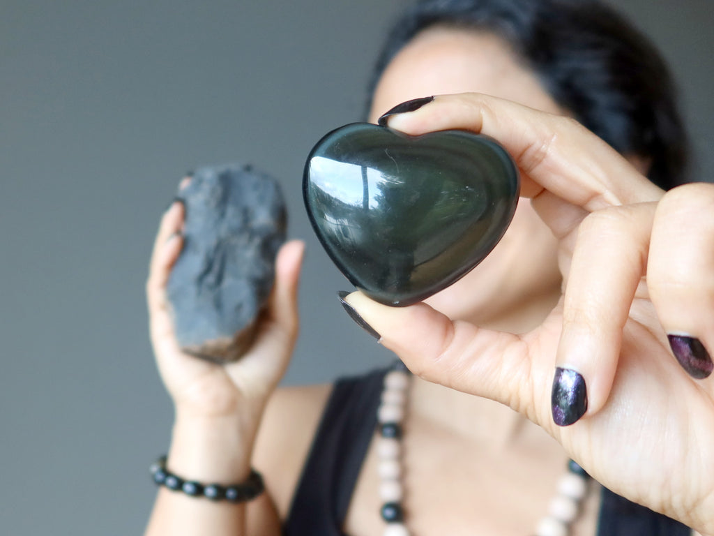 Sheila of Satin Crystals holding a polished heart and a rough Obsidian stone