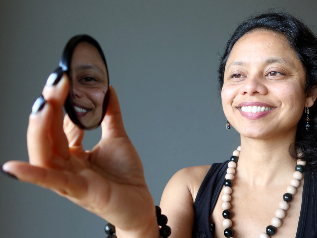 Sheila of Satin Crystals gazing at her reflection in an Obsidian mirror